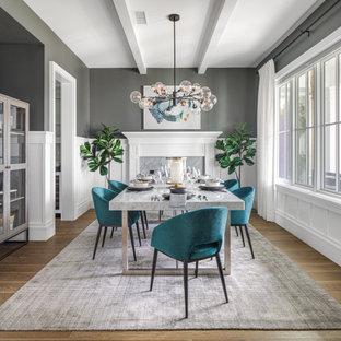 Großes, Geschlossenes Klassisches Esszimmer mit grauer Wandfarbe, hellem Holzboden, braunem Boden, Kamin, Kaminumrandung aus Holz, freigelegten Dachbalken und vertäfelten Wänden in Orange County