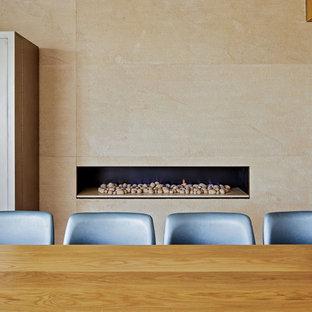 Immagine di una grande sala da pranzo aperta verso il soggiorno design con pareti beige, camino lineare Ribbon, cornice del camino in pietra, pavimento in pietra calcarea e pavimento beige