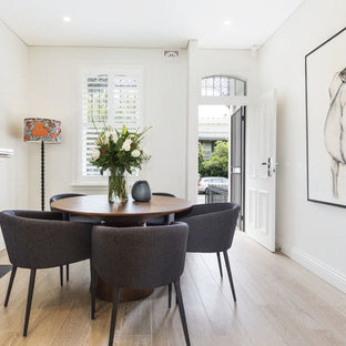 This is an example of a contemporary dining room in Sydney with beige walls, light hardwood floors and beige floor.