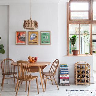 Foto di una sala da pranzo aperta verso il soggiorno eclettica di medie dimensioni con pareti bianche, pavimento in legno verniciato, camino classico, cornice del camino in metallo e pavimento bianco