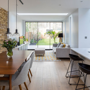 Mid-sized trendy medium tone wood floor and brown floor great room photo in London with red walls