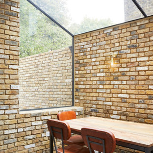 Foto di una piccola sala da pranzo minimal chiusa con pareti arancioni, pavimento in cemento e pavimento grigio