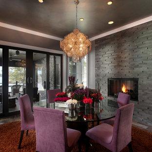 Exemple d'une grand salle à manger tendance fermée avec un mur gris, un sol en bois brun, un manteau de cheminée en pierre et une cheminée ribbon.