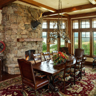 Dining room - rustic dining room idea in Denver with a stone fireplace