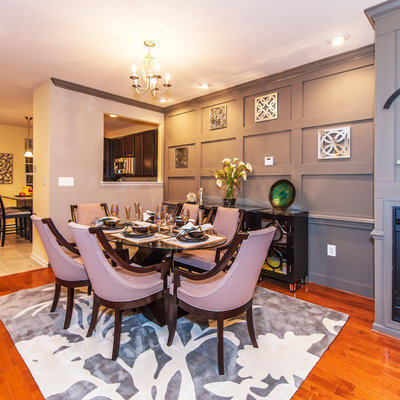 Inspiration for a timeless medium tone wood floor dining room remodel in DC Metro with gray walls and a standard fireplace