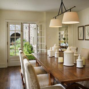 Cette photo montre une salle à manger chic avec un mur beige et un sol en bois foncé.
