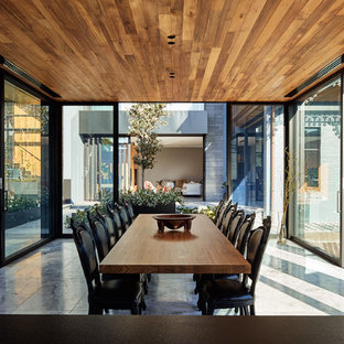 This is an example of a large contemporary kitchen/dining combo in Melbourne with limestone floors and grey floor.
