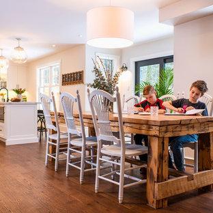 Foto di una sala da pranzo aperta verso la cucina country di medie dimensioni con pareti beige, pavimento in legno massello medio, camino sospeso, cornice del camino in metallo e pavimento marrone