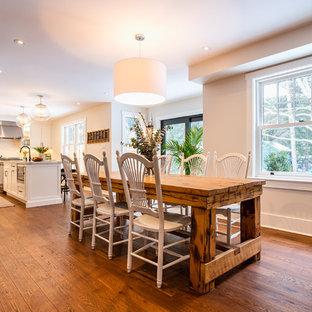 Bild på ett mellanstort lantligt kök med matplats, med beige väggar, mellanmörkt trägolv, en hängande öppen spis, en spiselkrans i metall och brunt golv