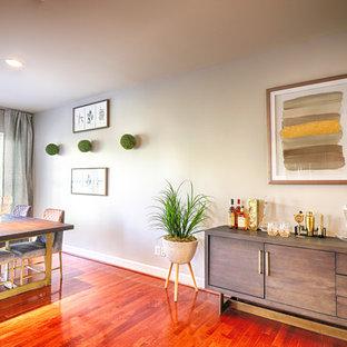 Foto di una grande sala da pranzo aperta verso il soggiorno chic con pavimento in legno massello medio, nessun camino, pavimento arancione e pareti grigie