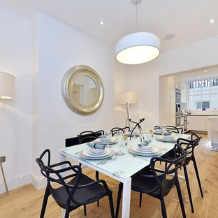 Large contemporary kitchen/dining room in London with white walls, light hardwood flooring and beige floors.