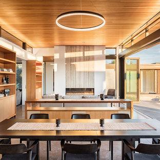 Ejemplo de comedor minimalista, abierto, con paredes blancas y suelo de cemento
