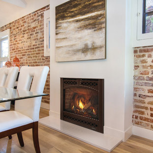 Mid-sized urban light wood floor and brown floor kitchen/dining room combo photo in Milwaukee with a standard fireplace and a plaster fireplace