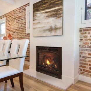 Imagen de comedor industrial con paredes rojas, suelo de madera clara, chimenea tradicional, marco de chimenea de hormigón y suelo beige