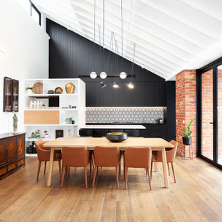 Photo of a contemporary kitchen/dining combo in Melbourne with white walls, medium hardwood floors, brown floor, exposed beam, vaulted and panelled walls.