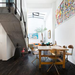 Imagen de comedor bohemio, de tamaño medio, con paredes blancas, suelo de madera oscura y suelo negro
