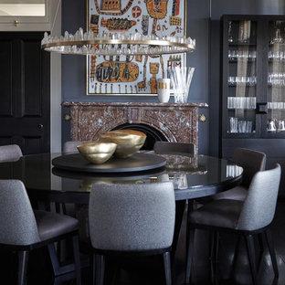 Cette photo montre une salle à manger éclectique fermée avec un mur gris, un sol en bois peint, une cheminée standard, un manteau de cheminée en pierre et un sol noir.