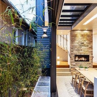 Immagine di una sala da pranzo minimal con pareti bianche, pavimento in cemento, camino lineare Ribbon, cornice del camino in mattoni e pavimento bianco