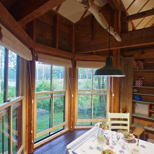 Imagen de comedor rural, pequeño, abierto, con suelo de madera pintada, estufa de leña, marco de chimenea de metal y suelo verde