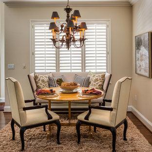 Immagine di una grande sala da pranzo aperta verso il soggiorno chic con pareti gialle, parquet scuro, camino classico e cornice del camino in pietra