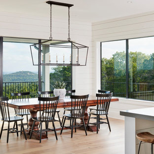 Example of a large country light wood floor and beige floor kitchen/dining room combo design in Austin with white walls