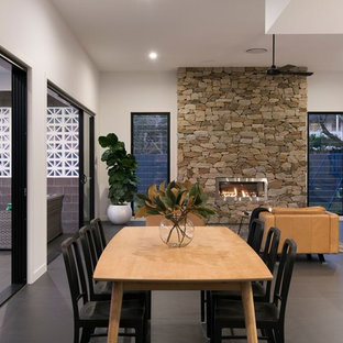 Contemporary open plan dining in Brisbane with white walls, a ribbon fireplace, a stone fireplace surround and grey floor.