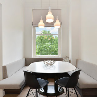 Example of a danish light wood floor dining room design in London with white walls