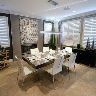 Idee per una sala da pranzo aperta verso il soggiorno chic di medie dimensioni con pareti grigie, pavimento in gres porcellanato, camino classico, cornice del camino piastrellata e pavimento beige