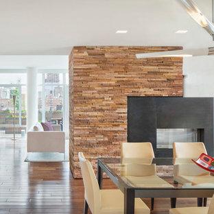 Großes Modernes Esszimmer mit weißer Wandfarbe, dunklem Holzboden, Tunnelkamin und Kaminsims aus Metall in New York