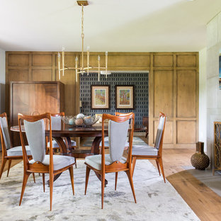 Diseño de comedor vintage, grande, cerrado, con chimenea tradicional, paredes grises, suelo de madera en tonos medios y marco de chimenea de hormigón