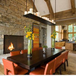 Diseño de comedor rústico con paredes blancas, suelo de madera en tonos medios, chimenea tradicional y marco de chimenea de piedra