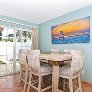 Idées déco pour une salle à manger ouverte sur la cuisine bord de mer avec un mur bleu, un sol en carrelage de céramique et un sol orange.