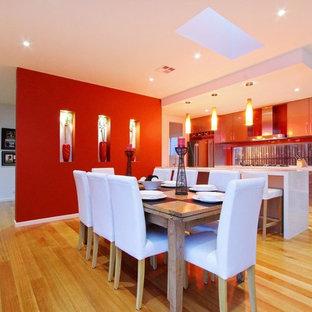 Ispirazione per una grande sala da pranzo aperta verso il soggiorno design con pareti rosse, parquet chiaro e pavimento nero