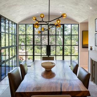 Exemple d'une salle à manger chic fermée et de taille moyenne avec un mur blanc, un sol en calcaire, un manteau de cheminée en pierre et un sol beige.