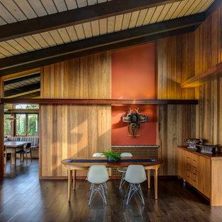 Inredning av en retro mellanstor matplats med öppen planlösning, med bruna väggar, mörkt trägolv, en standard öppen spis, en spiselkrans i betong och brunt golv