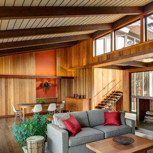 Diseño de comedor retro, de tamaño medio, abierto, con paredes marrones, suelo de madera oscura, chimenea tradicional, marco de chimenea de hormigón y suelo marrón