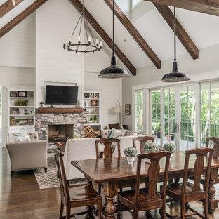 Foto de comedor de estilo de casa de campo, abierto, con paredes beige, suelo de madera en tonos medios, chimenea tradicional, marco de chimenea de piedra y suelo marrón