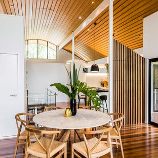 Design ideas for a contemporary dining room in Brisbane with white walls, medium hardwood floors and brown floor.