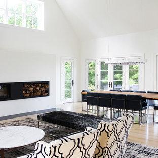 Foto di una sala da pranzo aperta verso il soggiorno minimalista di medie dimensioni con pareti bianche, parquet chiaro, camino lineare Ribbon e cornice del camino in intonaco