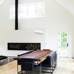 Photo of a mid-sized modern open plan dining in New York with white walls, light hardwood floors, a ribbon fireplace and a metal fireplace surround.