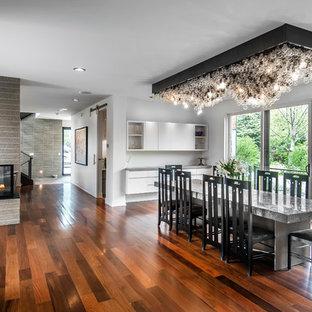 Ejemplo de comedor moderno, de tamaño medio, cerrado, con paredes blancas, suelo de madera oscura, marco de chimenea de hormigón, chimenea de doble cara y suelo marrón