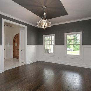 Idee per una grande sala da pranzo tradizionale chiusa con pareti grigie, parquet scuro e stufa a legna