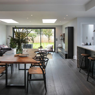 This is an example of a large contemporary open plan dining room in London with white walls, dark hardwood flooring, no fireplace and brown floors.