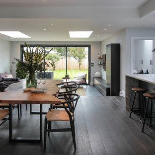 Неиссякаемый источник вдохновения для домашнего уюта: большая гостиная-столовая в современном стиле с белыми стенами, темным паркетным полом и коричневым полом без камина