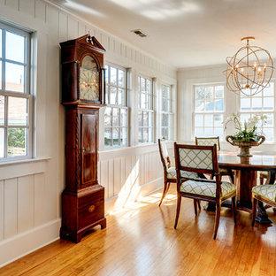 Diseño de comedor costero, grande, abierto, con paredes blancas, suelo de madera clara, chimenea tradicional y marco de chimenea de madera