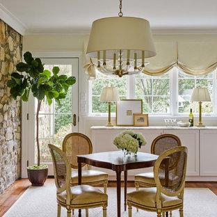 Foto di una sala da pranzo classica con pareti gialle, pavimento in legno massello medio e pavimento marrone