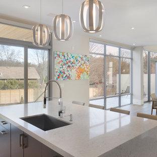 Immagine di un'ampia sala da pranzo aperta verso la cucina minimalista con pareti bianche, parquet chiaro, camino sospeso, cornice del camino in cemento e pavimento bianco