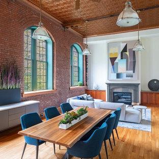 Aménagement d'une très grande salle à manger ouverte sur le salon industrielle avec un mur blanc et un sol en bois clair.