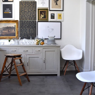 Example of an eclectic ceramic floor dining room design in London with white walls