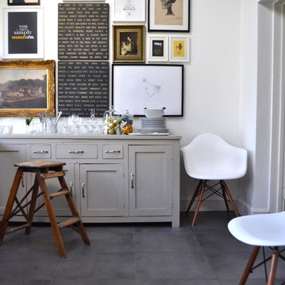 Example of an eclectic ceramic tile dining room design in London with white walls